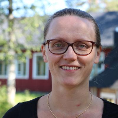 En kvinna med glasögon. Bakom henne skymtar några träd och ett rött hus.