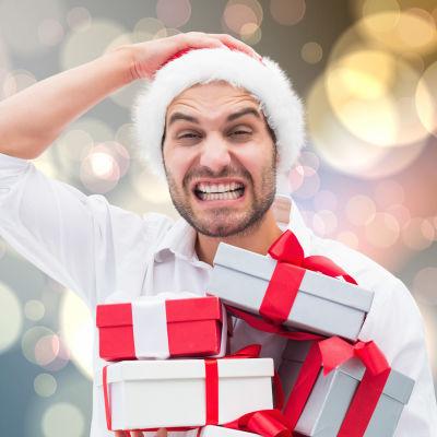 Stressad man med julklappar i famnen.