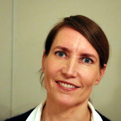 En kvinna med mörkt hår och med ett leende på läpparna står framför en ljus vägg.