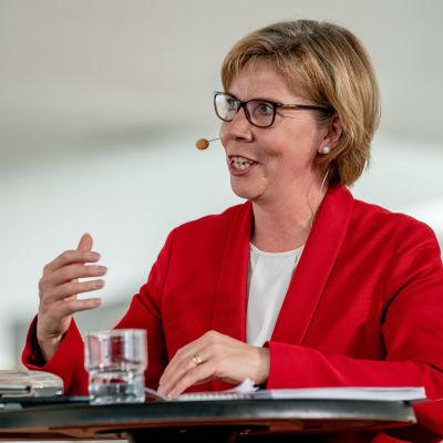 Anna-Maja Henriksson står vid ett bord och pratar under regeringens presskonferens i Helsingfors centrumbibliotek Ode den 3.6.2019.