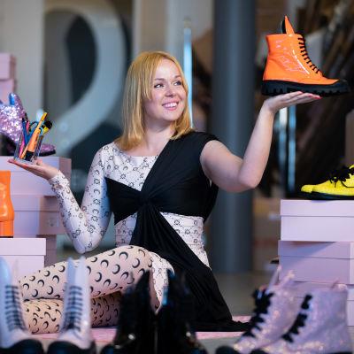 Skodesignern Minna Parikka sitter på golvet med skor framför sig. Hon har också skor i händerna.