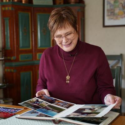 Eva Sparv bläddrar i ett fotoalbum