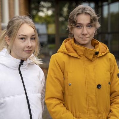Två personer står framför Ekenäs gymnasium.