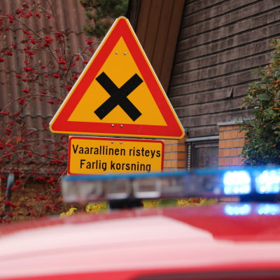 Ett trafikmärke som varnar för farlig korsning. I förgrunden syns taket av en brandbil med blinkande ljus.