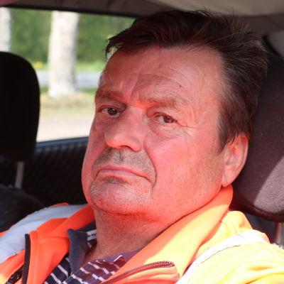 En medelålders man med kort mörkt hår sitter i en bil.