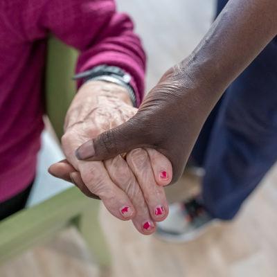 Vanhus ja hoitaja käsi kädessä.