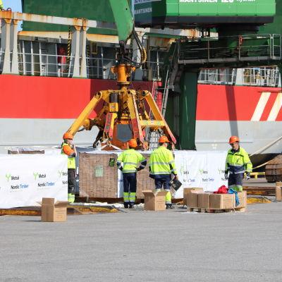 Hamnarbetare hjälper till med lastningen av ett fartyg i Kaskö hamn.