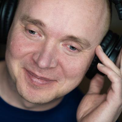 Petri Poikolainen lähikuvassa kuuntelee musiikkia luurit päässä.
