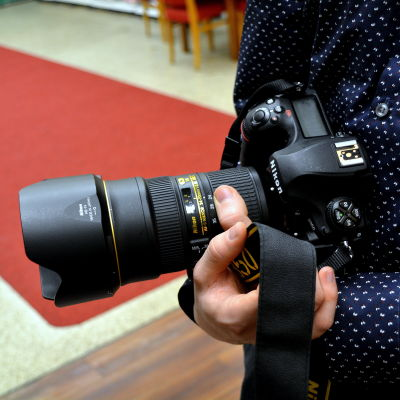 Fotograf med kamera i sin hand.