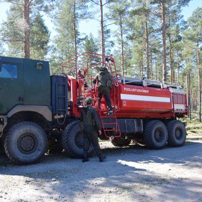 En bild på två beväringar som klättrar upp på en tankbil som fungerar som brandbil. Tankbilen är röd och det står Puolustusvoimat (Försvarsmakten) på den. Runt omkring den finns det tallskog.