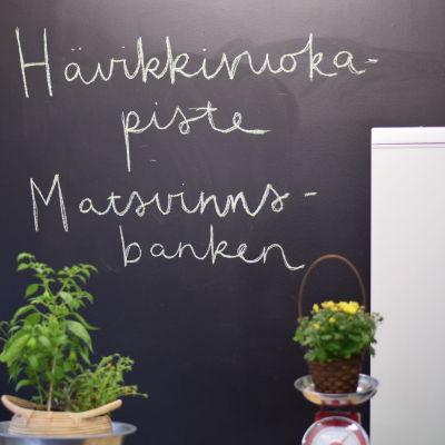 """en svart väggtavla som det står """"hävikkiruokapiste matsvinnsbanken"""" på"""
