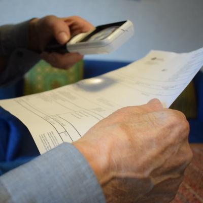 En gammal hand håller i en faktura och i andra handen ett förstoringsglas.
