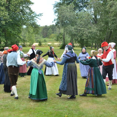 Människor i folkdräkt dansar folkdans i en park.