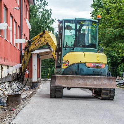 Grävmaskin gräver utanför skolhus