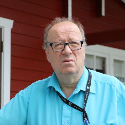 En skallig medelålders man med ljusblå pikéskjorta lutar mot ett räcke och ser bekymrad ut.