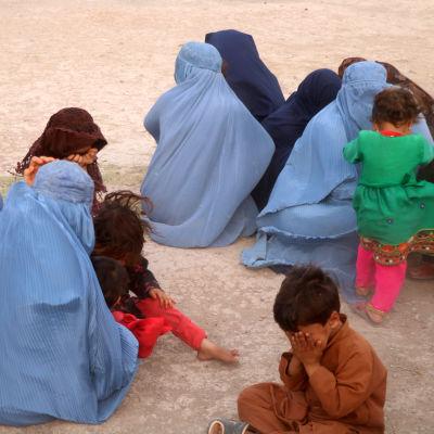 Naisia ja lapsia istumassa maassa.