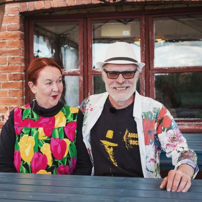 Hymyilevä pariskunta, Aslak Christiansson ja Leena Vilenius, taustalla punatiilinen navetan seinä.