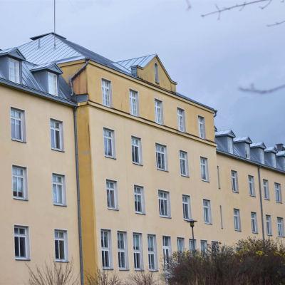 Ett stort rappat, gult hus i fyra våningar. Gammalt sjukhus.