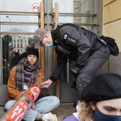 Poliiis yrittää poistaa mielenosoittajaa portailta.