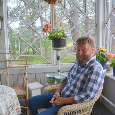Berndt Ardell är en man med skägg och blå-vitrutig skjorta. Han sitter i en korgstol på verandan.