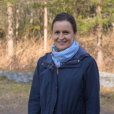 En kvinna ler in i kameran. Bakom henne syns en skog.