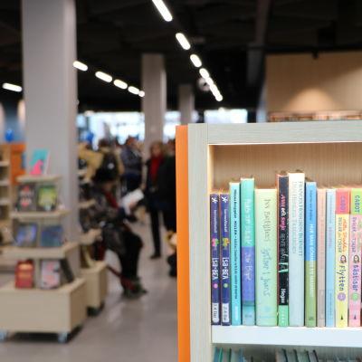 En bokhylla i Degerö bibliotek med suddig bakgrund.