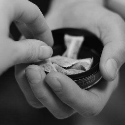 En hand tar en prilla snus från en dosa som en annan person håller fram.