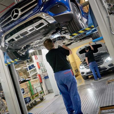 Bilbyggare vid Nystads bilfabrik bygger ihop en mörkblå bil som hänger från taket.