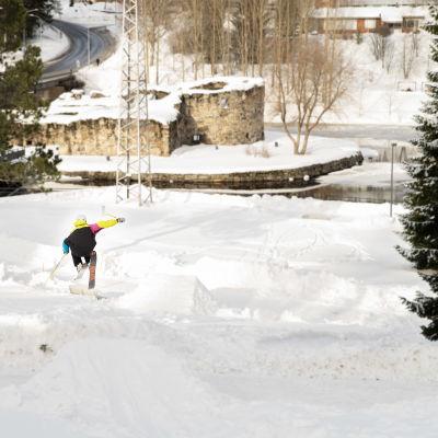 Ari-Matti Vakkuri hyppää suksilla Kajaanin jokipuistossa.