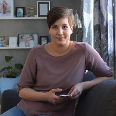Elisabeth Sundqvist från Jakobstad sitter hemma i soffan med sin smarttelefon i handen.