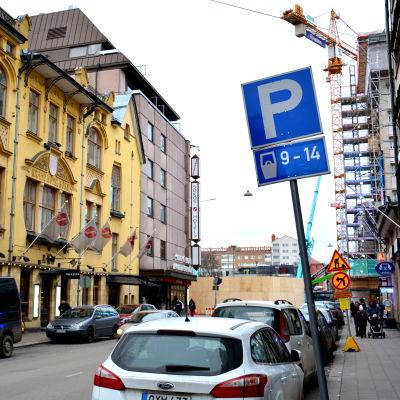 köpmansgatan med fokus på en parkeringsskylt och med gult hus till vänster och torget i bakgrunden
