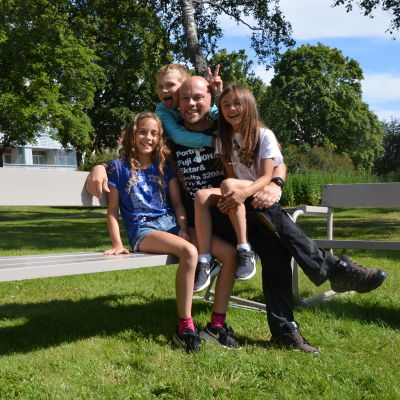 En pappa sitter på en bänk med sina tre barn.