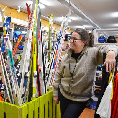 En kvinna bredvid en ställning med skidor.