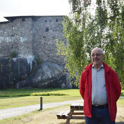 En man står i röd rock och skjorta. I bakgrunden syns en stenborg som är Raseborgs slottsruin.