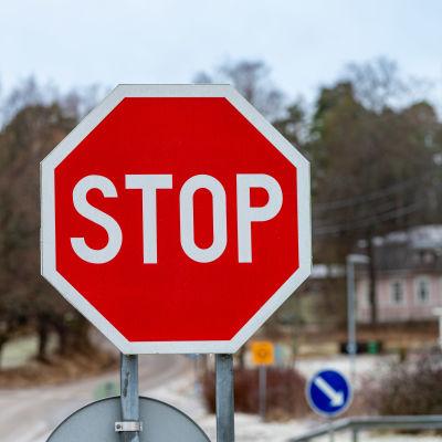En röd-vit trafikskylt som betyder att bilar måste stanna.
