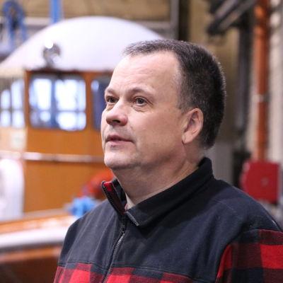 En medelålders man med aningen grått kort hår står inne i en verkstad.