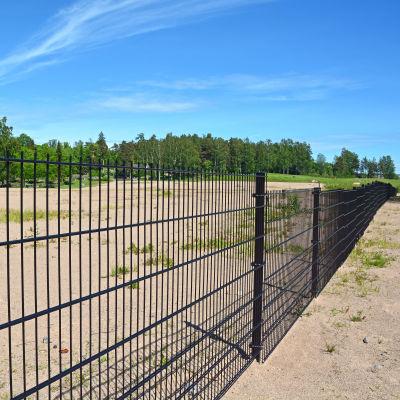 Staket i förgrunden, begravningsplats i bakgrunden.