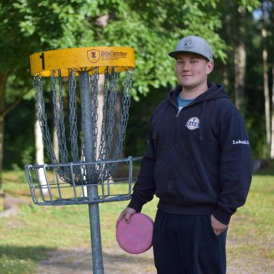 Frisbeegolfklubben Raaseporin Korillas ordförande Emil fageström vid den första korgen på banan i Karis.