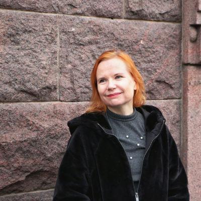 Maija Puromies tittar bort från kameran. Hon står framför en tegelvägg. Hon har orange hår och en svart jacka.