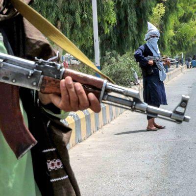 Kaksi Taliban-taistelijaa seisoo tiellä. Kuvassa etualalla on toisen taistelijan pitelemä rynnäkkökivääri.