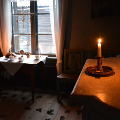 Ett ljus brinner i ett av stugorna i Klosterbacken.