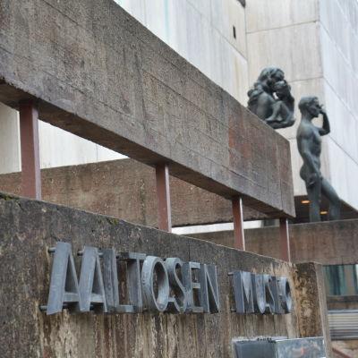 Närbild på text där det står Wäinö Aaltosen museo, utanför muséet. Två statyer står i bakgrunden.