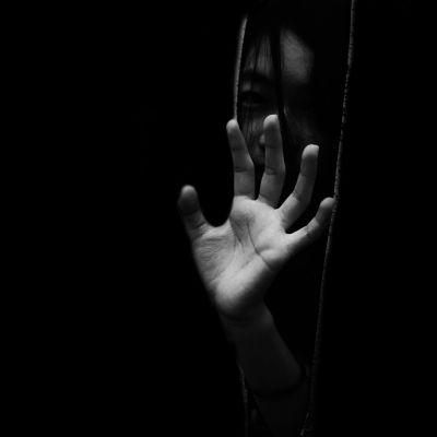 En kvinna med handen framför ansiktet. Svartvit bild med svart bakgrund.