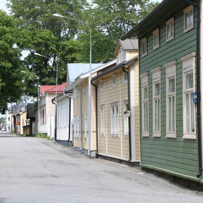 En gata med gamla trähus i olika färger.