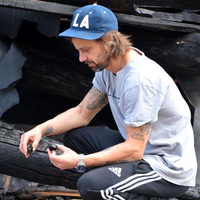 Man undersöker träbitar efter husbrand.