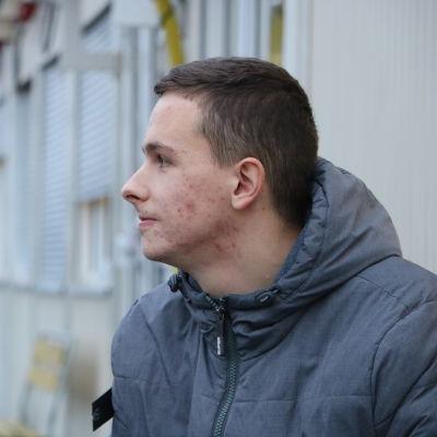En ung man med kort mörkt hår sitter på en bänk framför en barack.