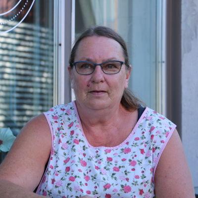 En kvinna med glasögon sitter framför ett fönster.