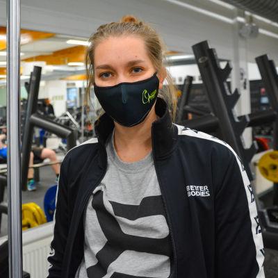 Ung kvinna med munskydd i ett gym.