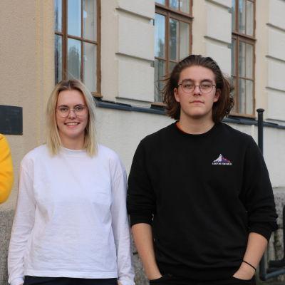 Två pojkar och en flicka står framför en skolbyggnad.