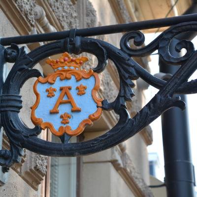Åbo stads vapen på en gammaldags lampställning som är fastskruvad i en yttervägg.